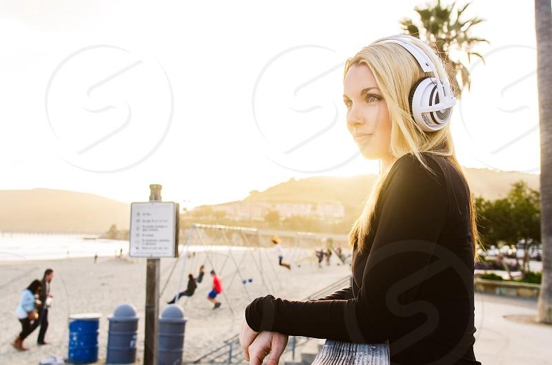 Model wearing headphones by beach. photo