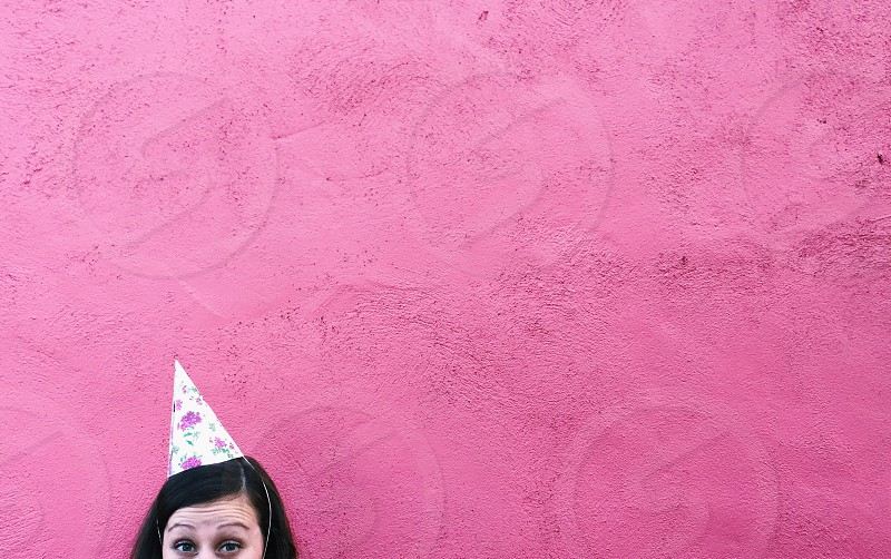 woman wearing white and pink birthday hat photo