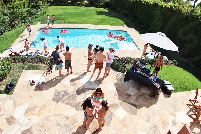 people standing around a backyard swimming pool surrounded by green hedges photo