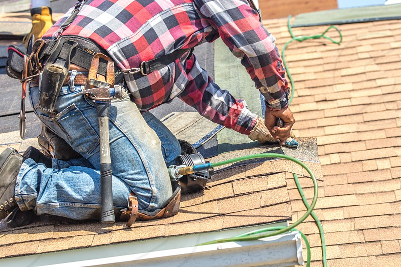 Worker putting shingles on roof photo