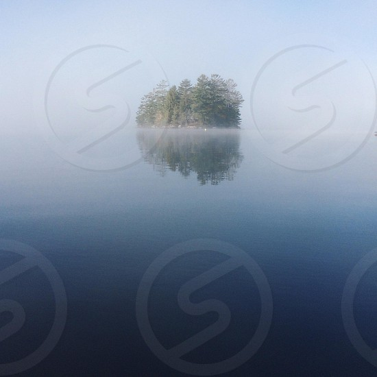 islet of green tall trees with mists surrounded by calm blue water photo