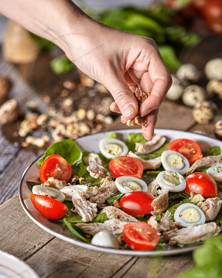 Woman put nuts to a freshly prepared homemade salad from organic ingredients on a wooden board. Natural freshly organic dieting food. photo