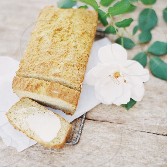brown slice pastry beside white flower on brown wooden table photo