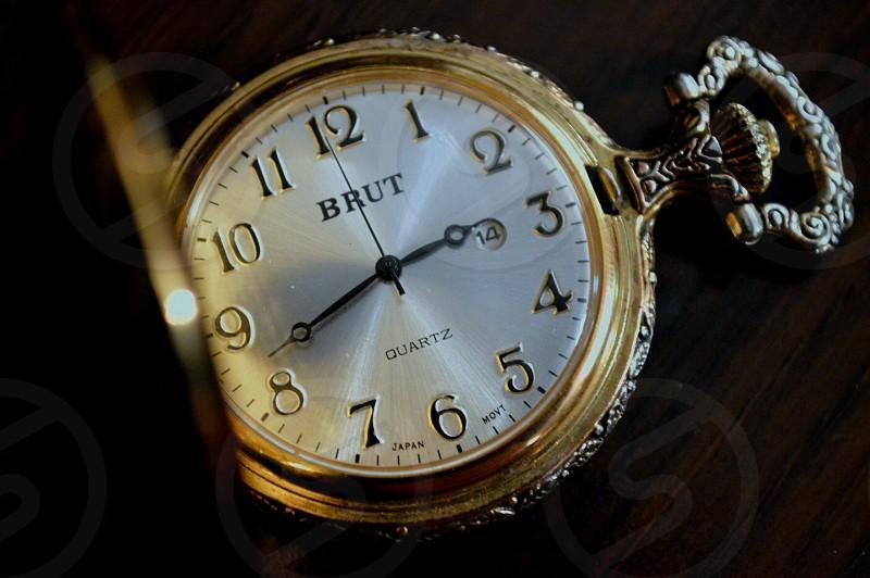 gold pocket watch at 2:42 photo