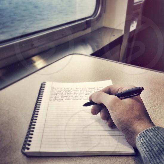 man writing on  notebook photo