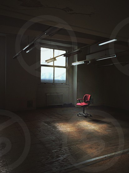 red office chair by square window beneath hanging fluorescent lights photo