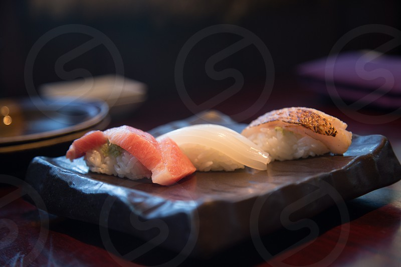 sushi rice and meat on black ceramic square plate over brown wooden panel photo