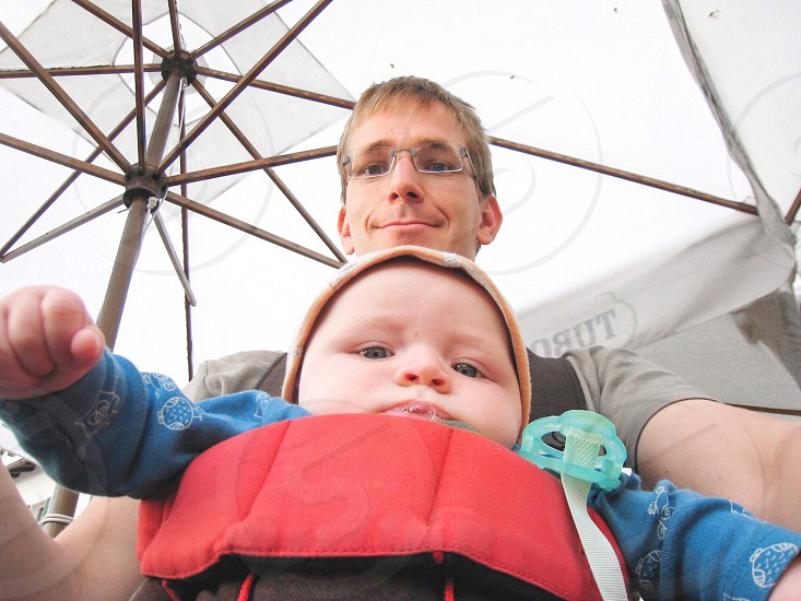 man with his baby under white parasol photo