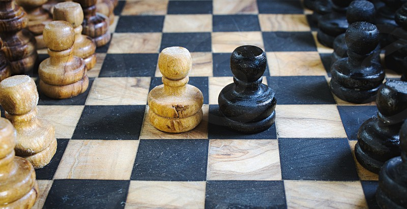Old olive wood chess set board with staunton pieces and black and white pawns battling head-to-head photo