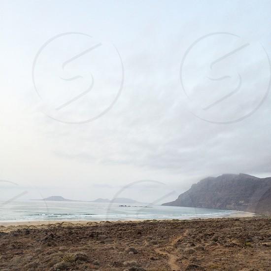 seashore with mountains view photo