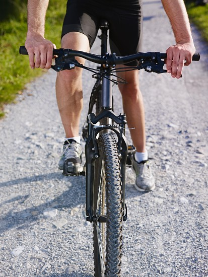 riding; bicycle; bike; biker; biking; man; road; 20s; active; activity; adult; adventure; brake; braking; caucasian; cropped; country; countryside; cycle; cycling; cyclist; dirt; exercising; field; fitness; hands; helmet; leisure; low section; male; nature; one; outdoors; path; people; person; ride; sport; sportswear; summer; tire; track; trail; training; unrecognizable; workout; young photo
