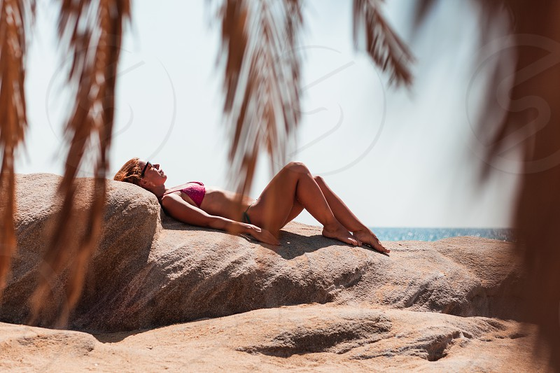 Young woman tanning on the beach photo