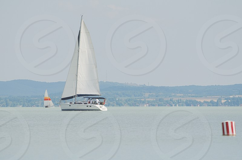 White Sailboat on Lake Balaton with Red and White Striped Buoy photo