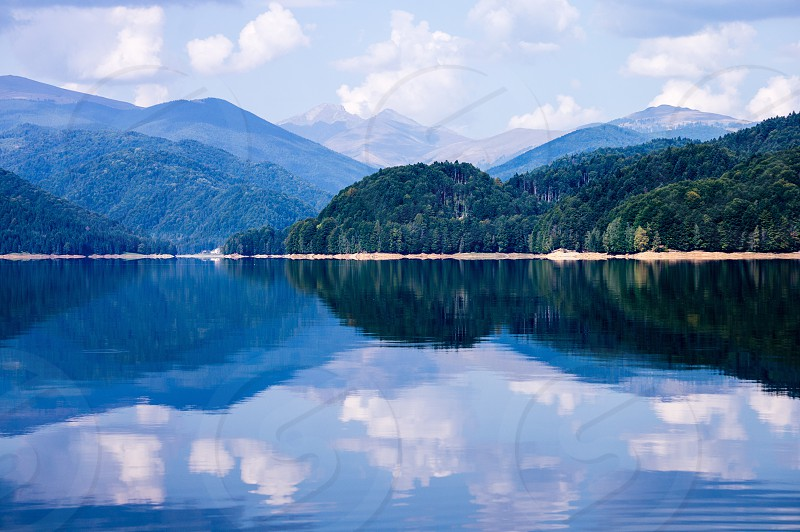 landscape photo of green mountain in front of calm body of water during daytime photo