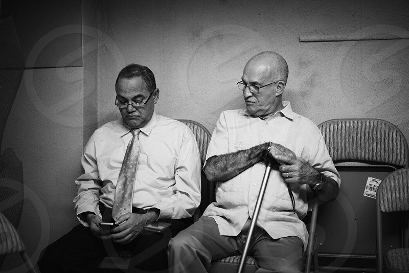 grayscale photo of two man sitting on chairs photo
