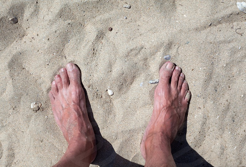 Details of man's legs standing on sand. photo