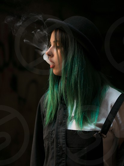 Emo girl smoking cigarette.Street punk or hipster woman with blue colorful dyed hair hat piercinglensesears tunnels and unusual hairstyle stands in backyard. beautiful smoke. photo