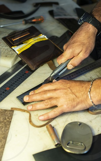 Tailor process leather in workshop. Making leather products. photo
