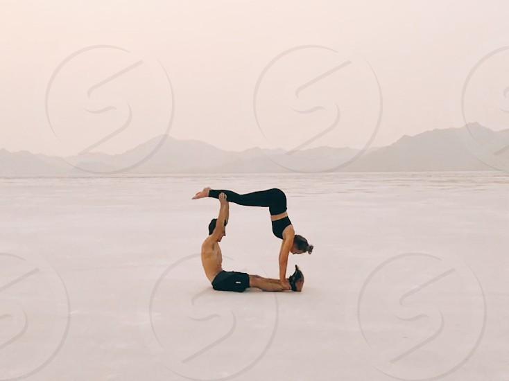 Acro yoga yoga couple man woman salt flats athletic fitness healthy workout photo