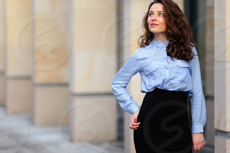 Brunette smiling woman standing near the wall of building looking forward into camera photo