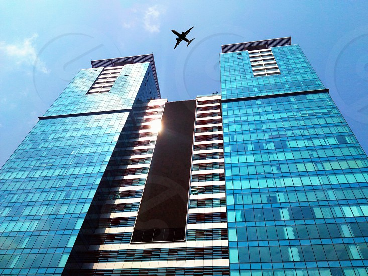 airplane flying above blue building during daytime photo