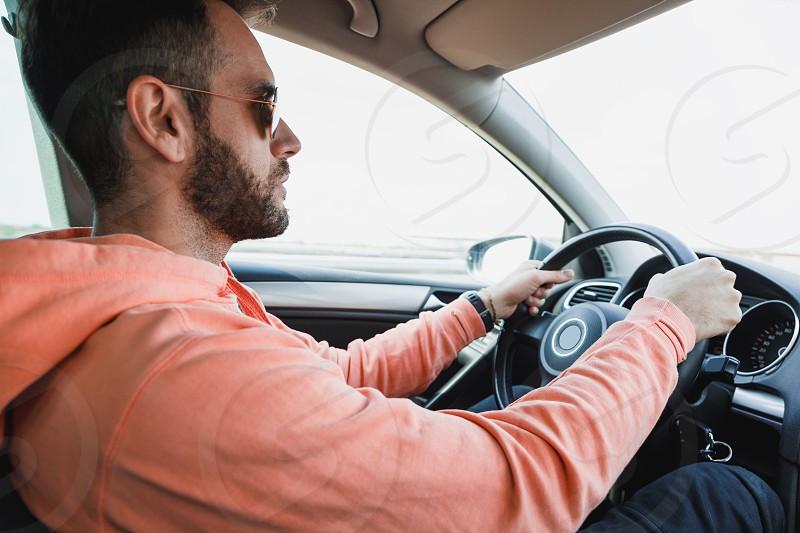 Young man driving a car interior shot photo