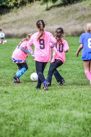 group of girls playing soccer photo