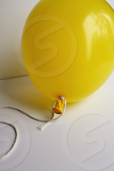 yellow balloon on a white background party tied with white cotton string photo