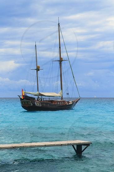 pirates inspired wood sailboat anchored turquoise sea Formentera photo