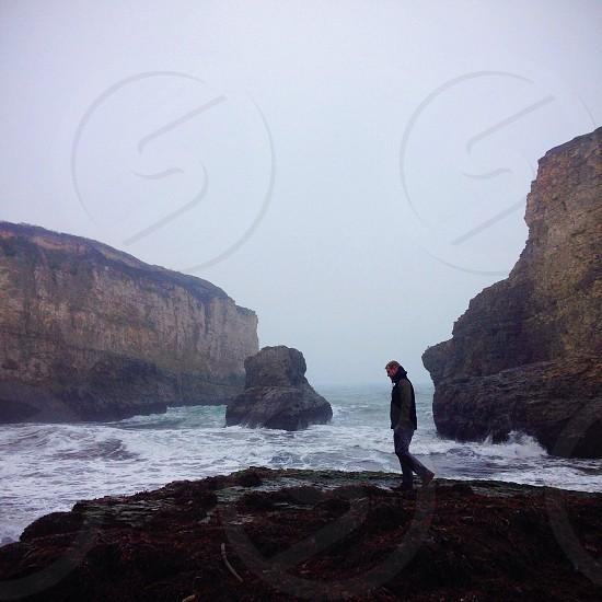 man walking on rock formation photo