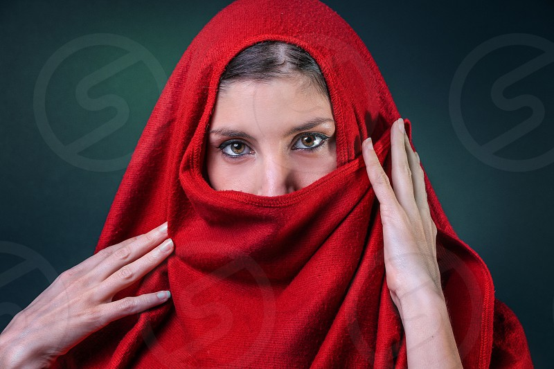 Oriental Woman covered with a red Poncho  photo
