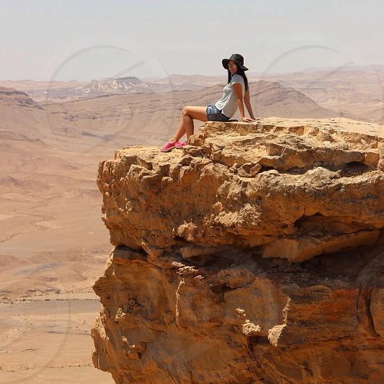 woman sitting on mountain rock photo