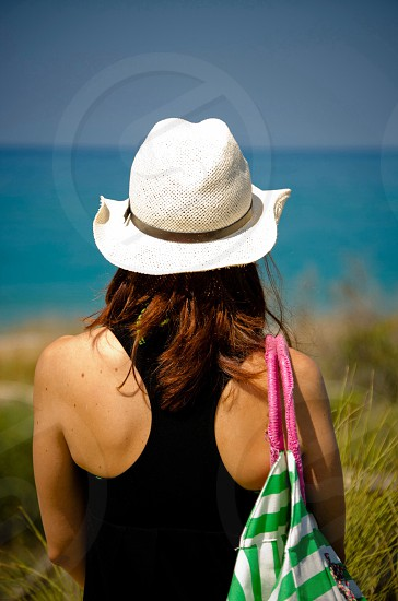 brunette woman in black halter top and white woven hat standing in green grass overlooking blue ocean with green and white striped bag over shoulder photo