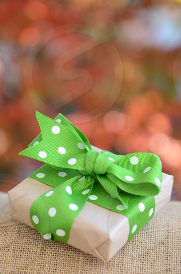 Present brown craft paper green and white polka dot ribbon burlap birthday Christmas gift package photo