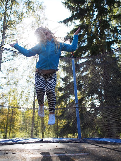 Kid child playing outdoor girl trampoline autumn jumping photo
