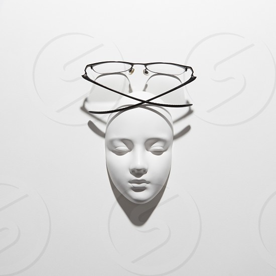 Plaster face mask with elegant glasses above it on a white background with soft long shadows copy space. Flat lay. Optics fashion style. photo