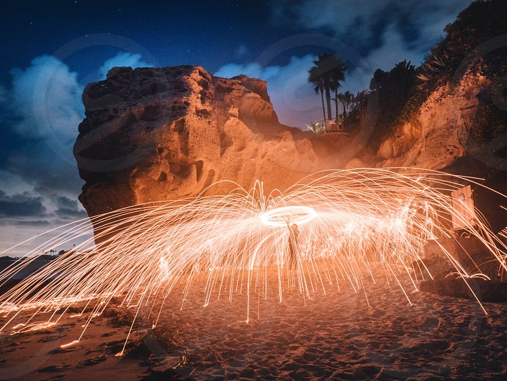 person holding sparklers at the beach photo
