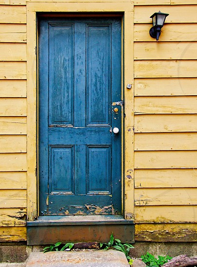 Bright blue wooden door on a house with yellow siding  photo