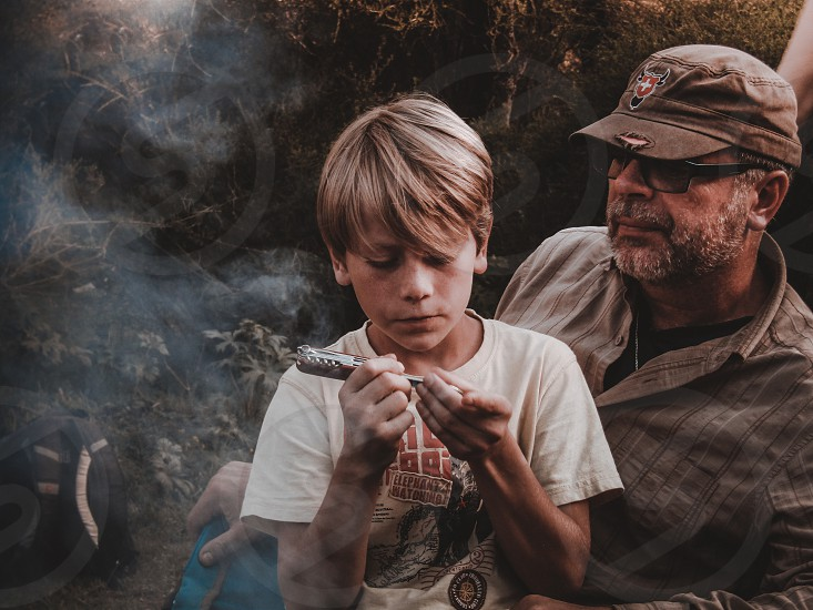 father son camping just chilling by camp fire  photo
