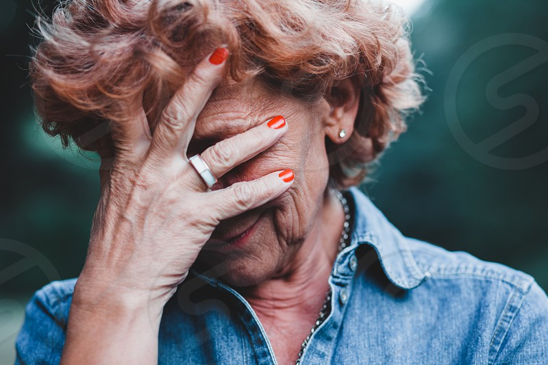 Older women worrying with her hands over her face photo