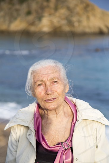 Portrait of the happy elderly woman against the sea in sunny spring day. photo