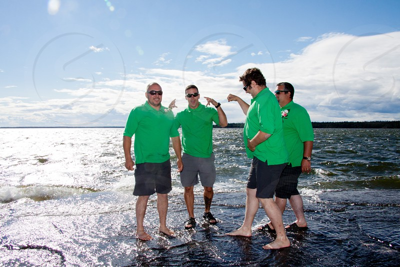 4 men in green polo shirt standing on the seashore under the blue sky photo