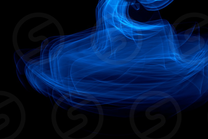 Light painted glowing abstract blue curved lines on a black background photo