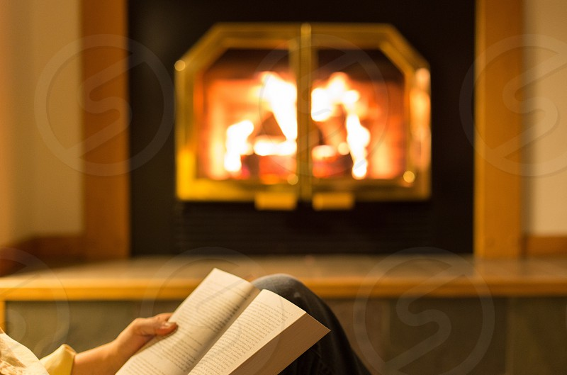 A man reads a book in front of a fire photo