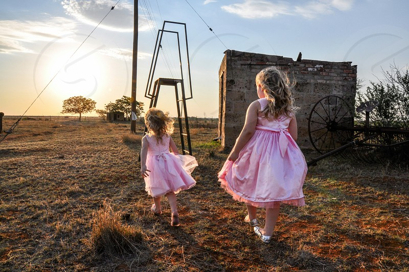 sunset spring  two children in pink dresses photo