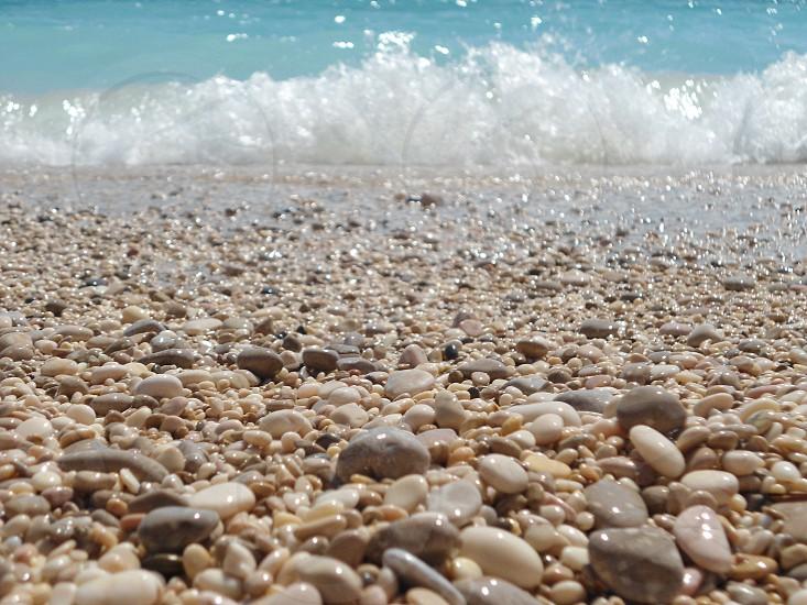 white pebble stones on sea shore photo