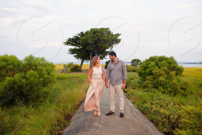 woman in light brown sleeveless dress walking in concrete pathway white holding hand of man in grey dress shirt while looking each other under white clouds during daytime photo
