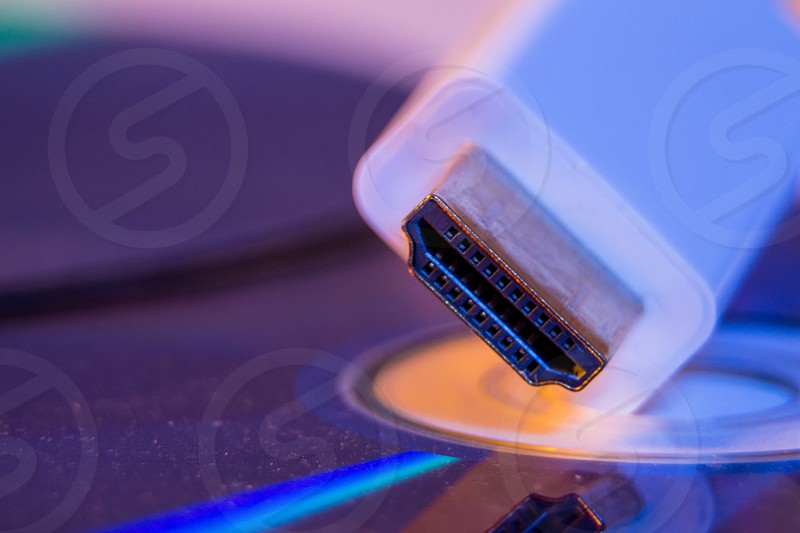 Closeup of white HDMI cable with it's reflection on blank disc. photo