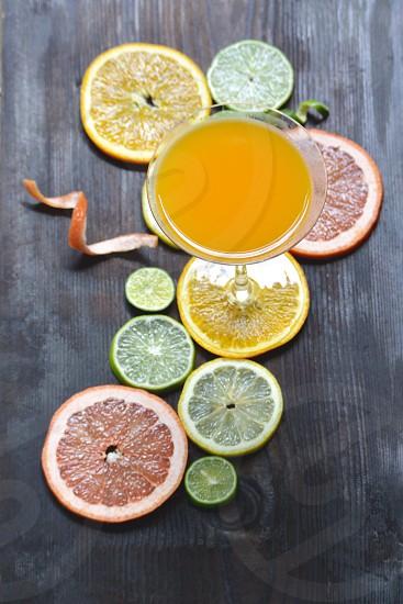 clear wine glass beside sliced lemon lime photo