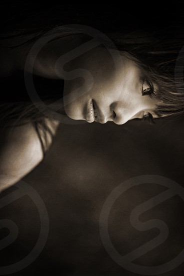 sepia photo of girl with long eyelashes and long hair covering eyebrows and wearing lip balm looking into the horizon photo